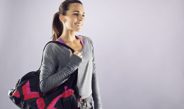 Female athlete with gym bag looking away smiling