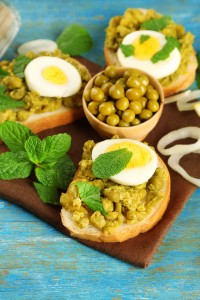 Sandwiches with green peas paste and boiled egg with napkin on color wooden background