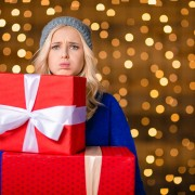 Woman holding gift boxes over holidays lights background