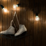 ice skates against an weathered wooden wall with lightbulbs