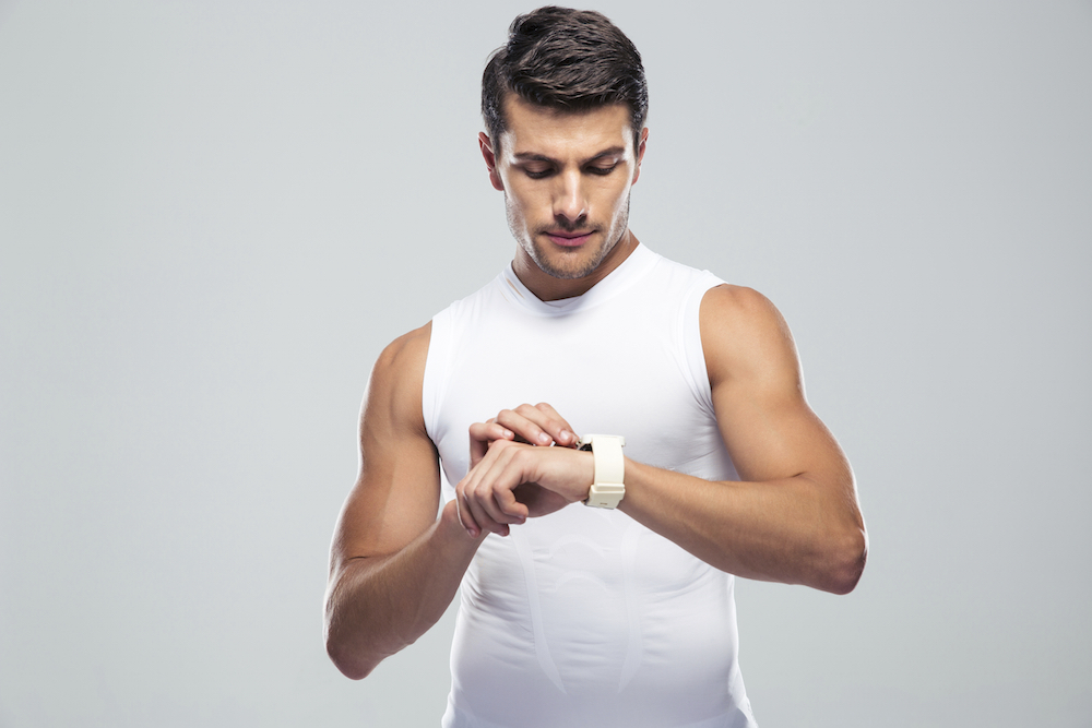 Handsome fitness man using smart watch
