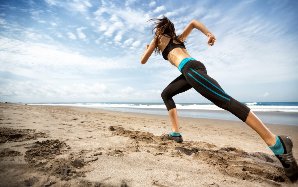 sports woman running on seaside