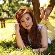 Beautiful red hair woman lying on grass at the park
