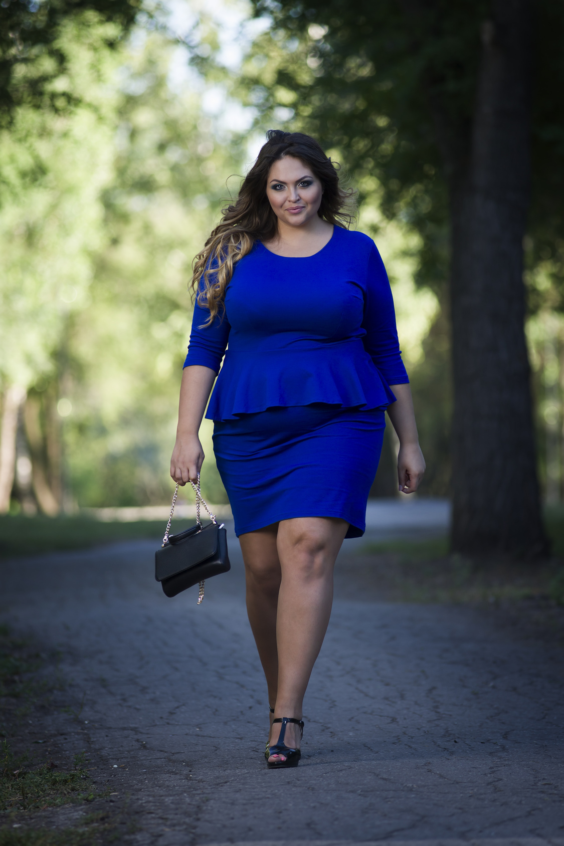 Young beautiful caucasian plus size fashion model in blue dress outdoors, xxl woman on nature