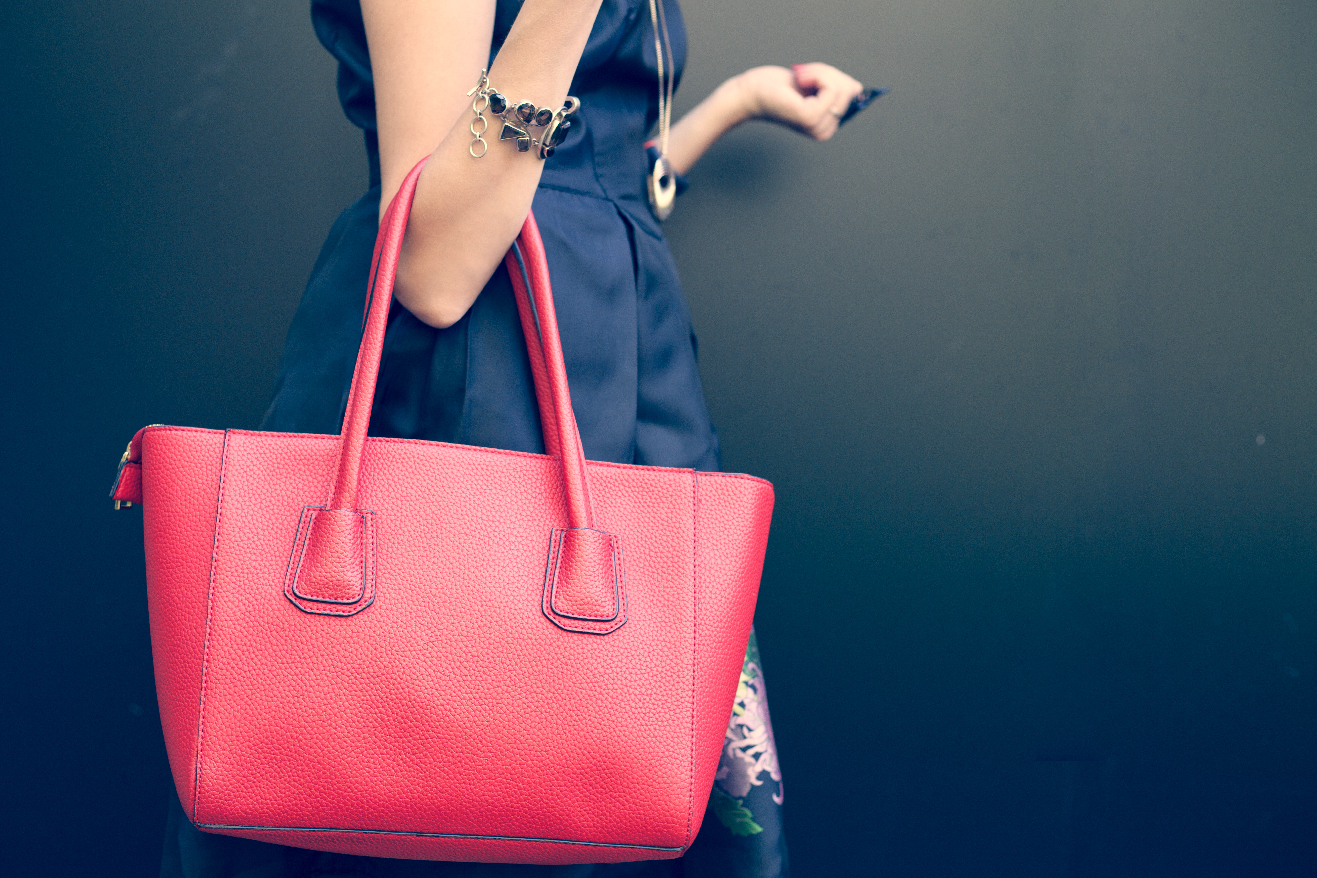 Fashionable beautiful big red handbag on the arm of the girl in