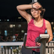 Healthy fit sporty woman exhausted and dizzy rising forearm to forehead at home on exercise static bike after daily female workout routine. Sporty tired girl health weekly beneficial habits.