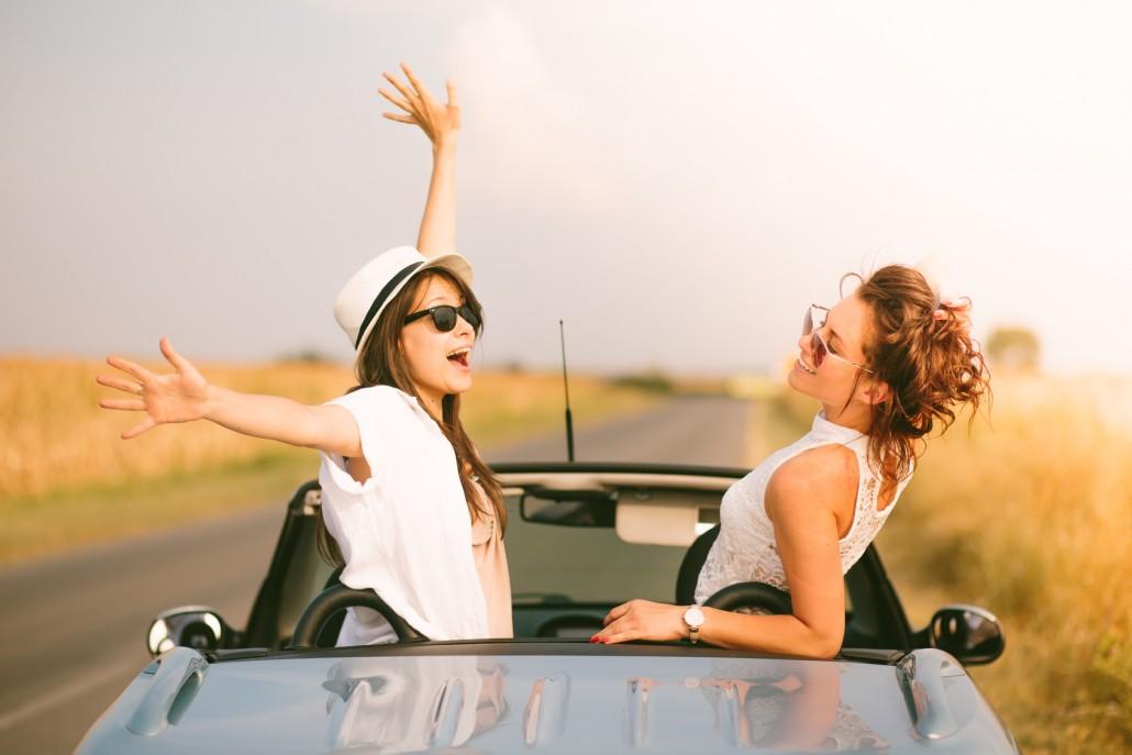 Two happy female friends enjoying road trip in their cabriolet