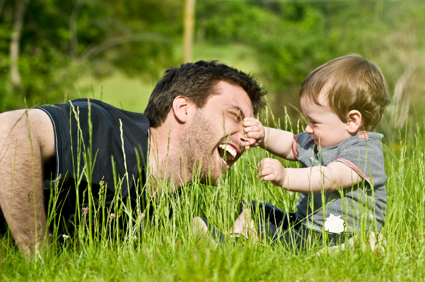 cute little child playing and joking in countryside with dad during summer