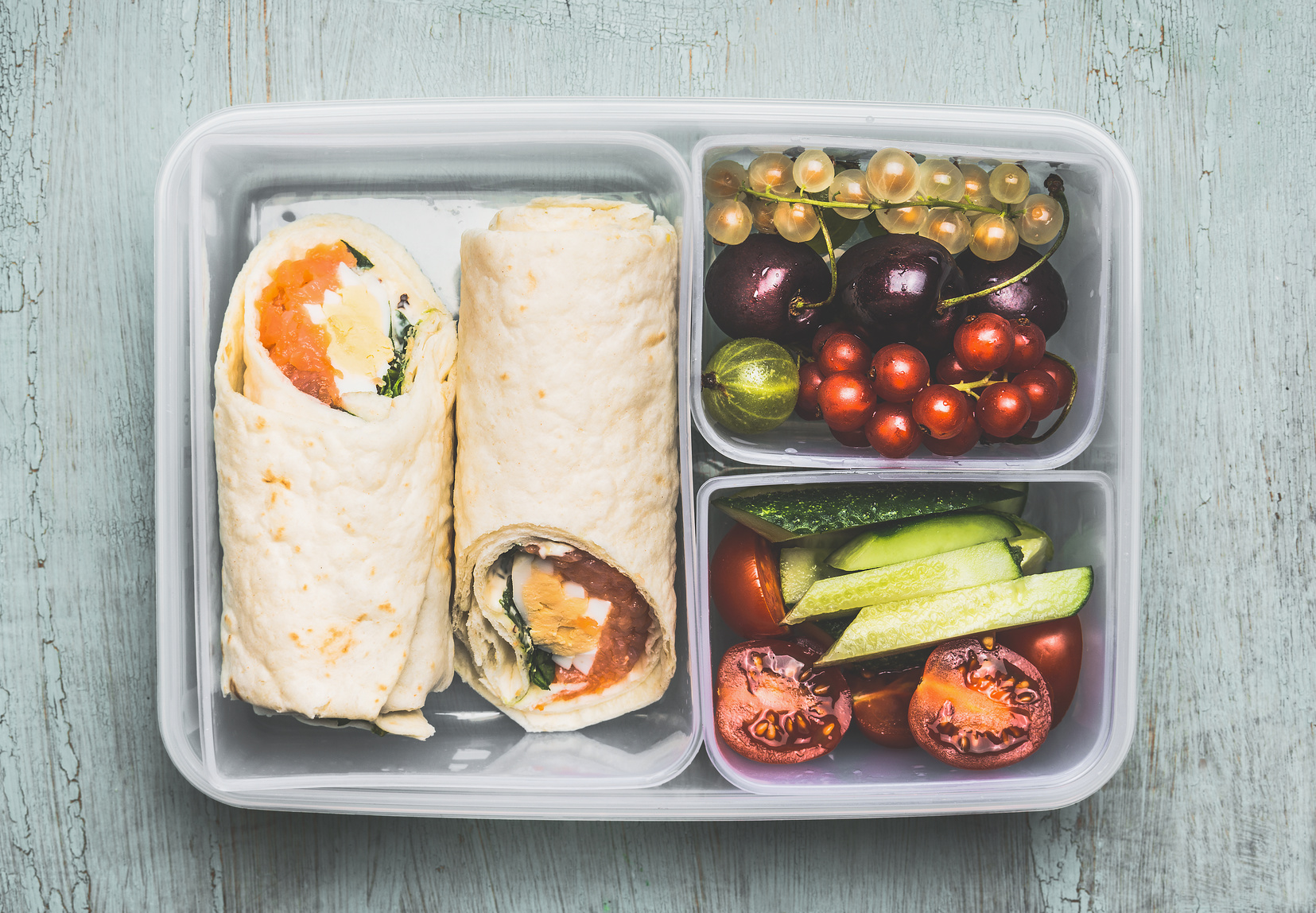 Healthy lunch box with vegetarian tortilla wraps, chopped vegetables and fruits on wooden background , top view.