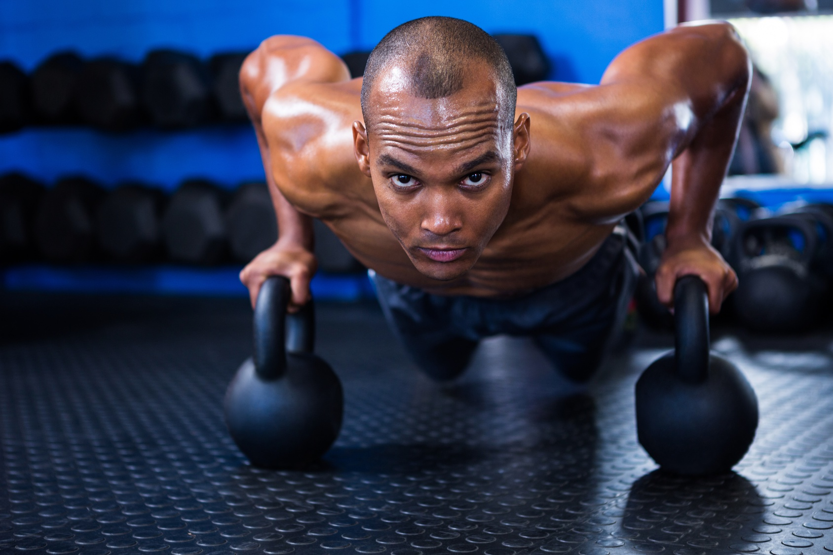 Man doing push-ups with kettlebells