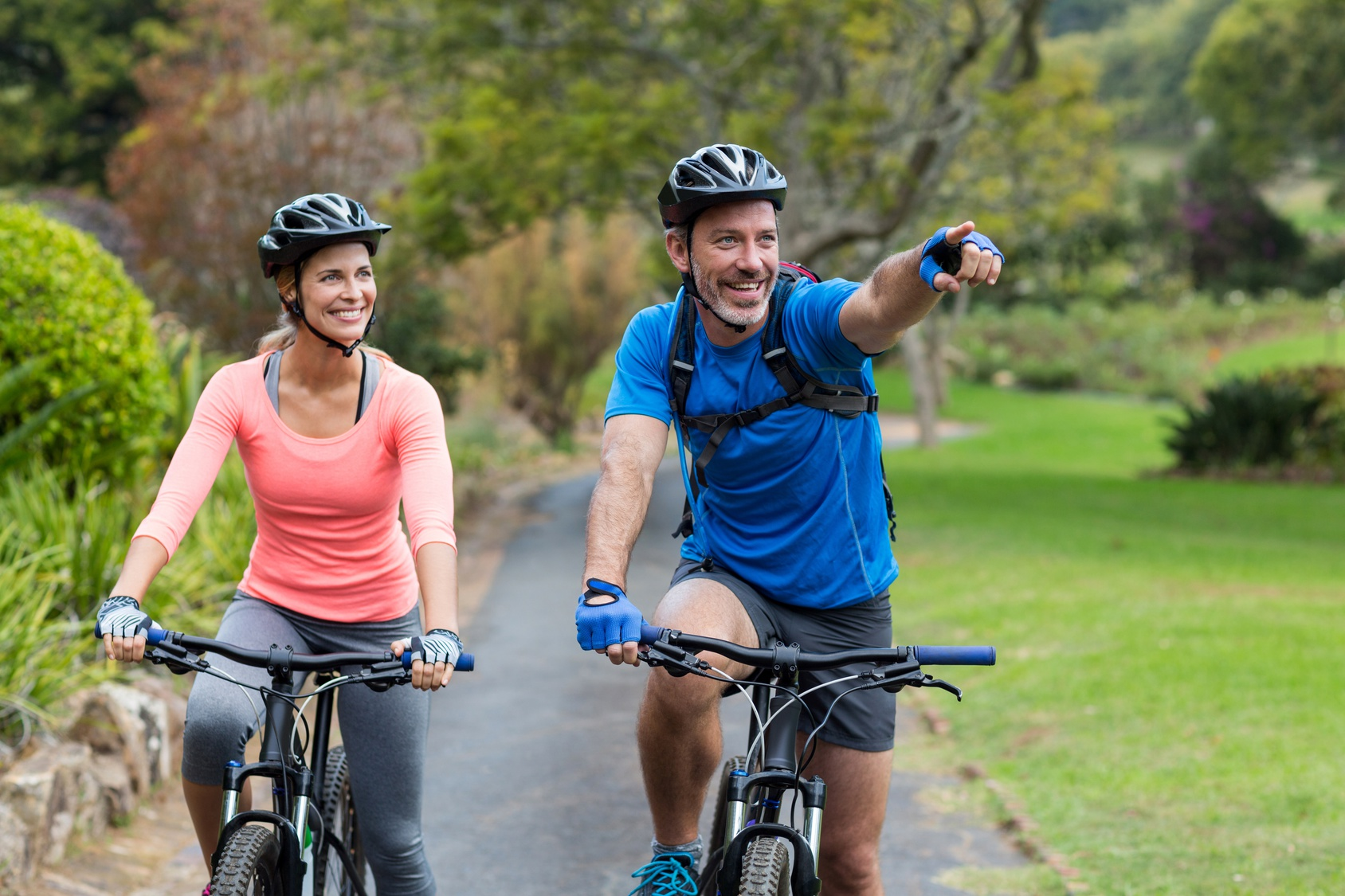 Athletic couple pointing while riding bicycle