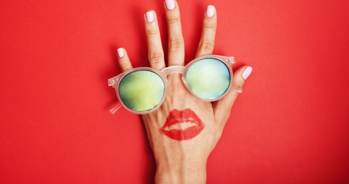 woman hand holding sunglasses on bright background, cosmetic summer vacation concept