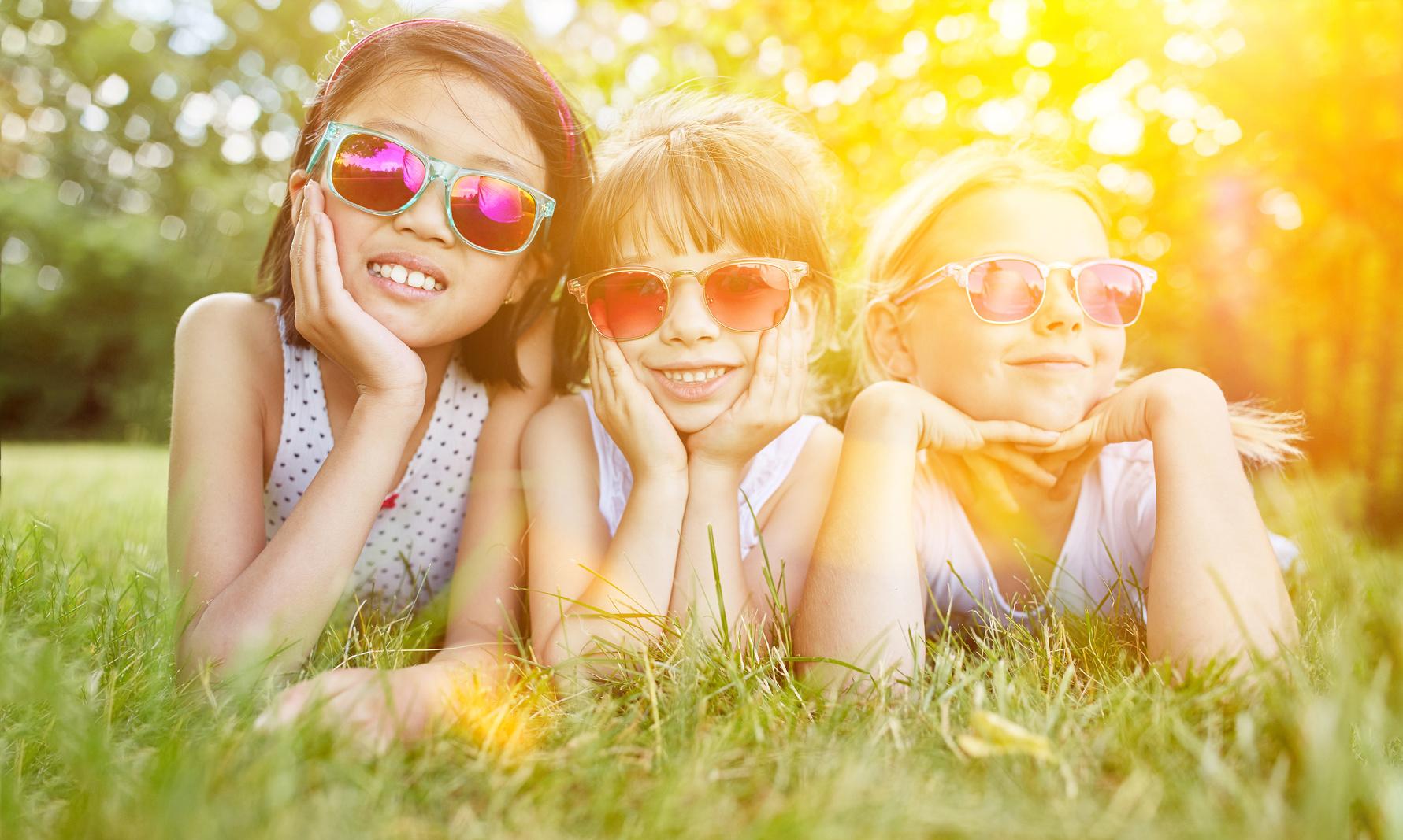 Mädchen mit Sonnenbrille auf Wiese im Sommer