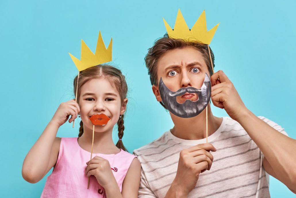 Dad and child are holding paper crown