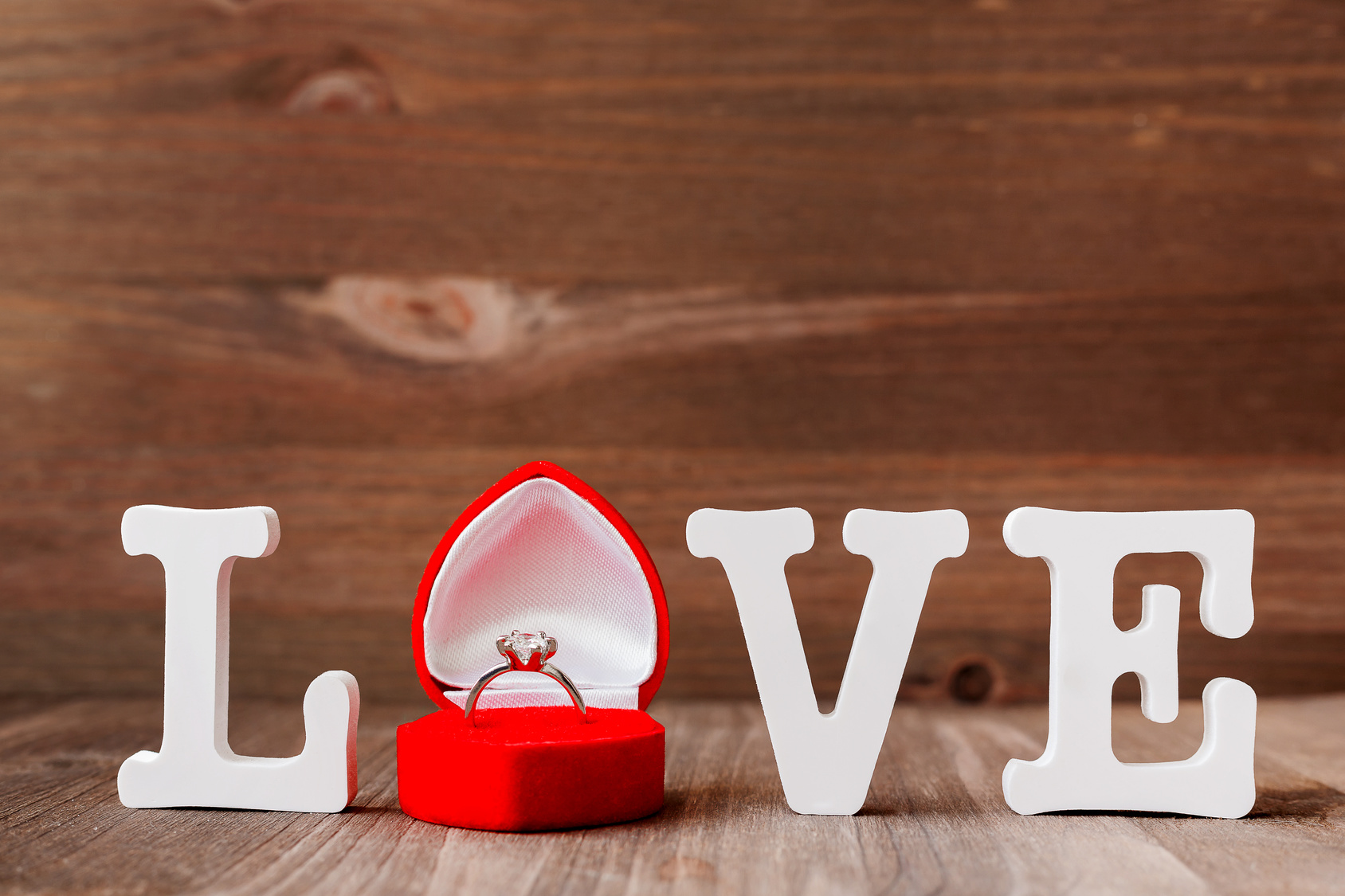 Word LOVE and diamond engagement ring in red gift box on wooden background.