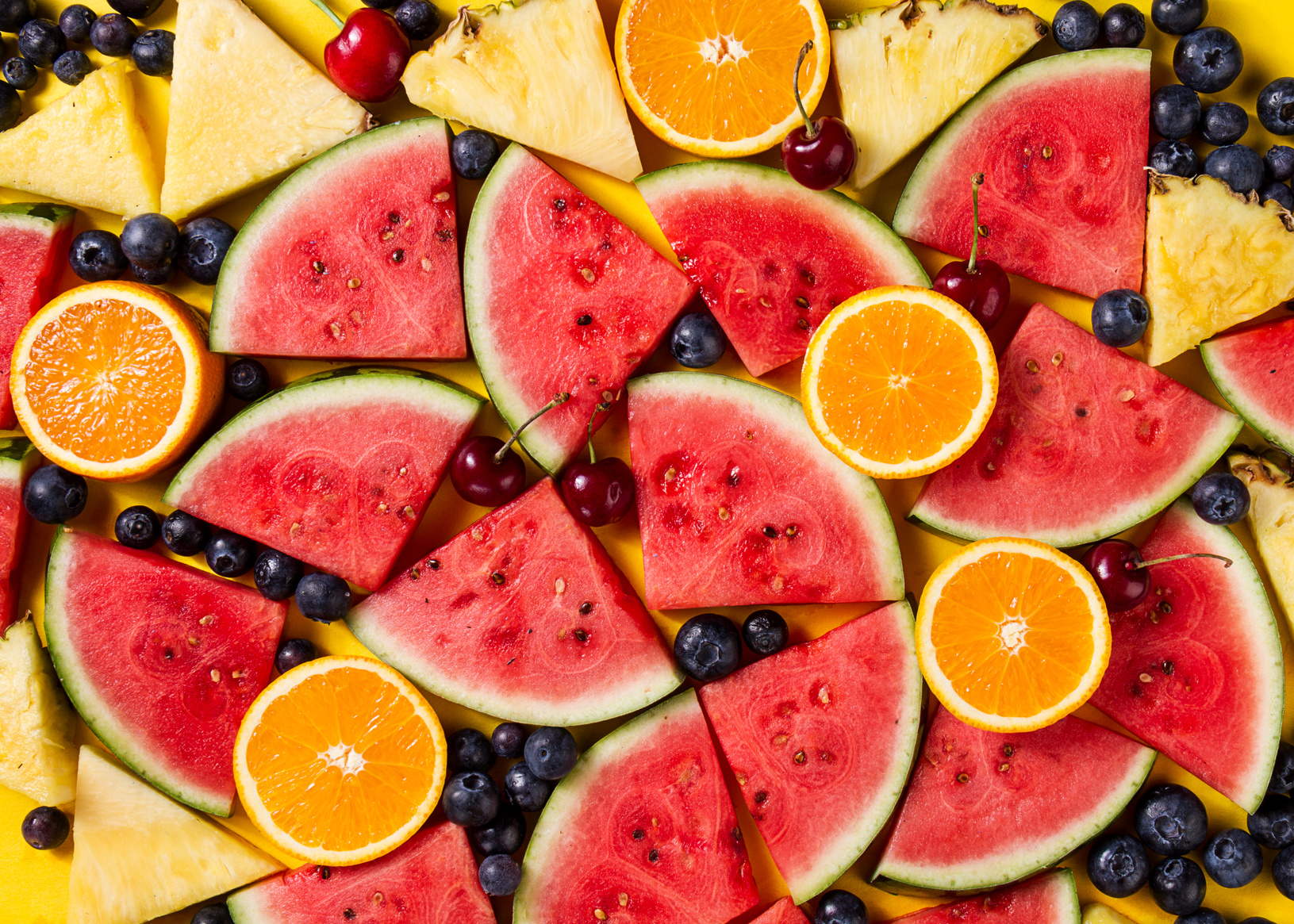 Beautiful pattern with fresh watermelon slices, pineapple, cherries and blackberries on yellow bright background. Top View.