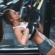 Women doing push ups training arms with trx fitness straps in the gym