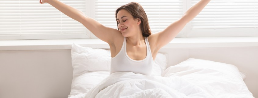 Happy Woman Stretching On Bed
