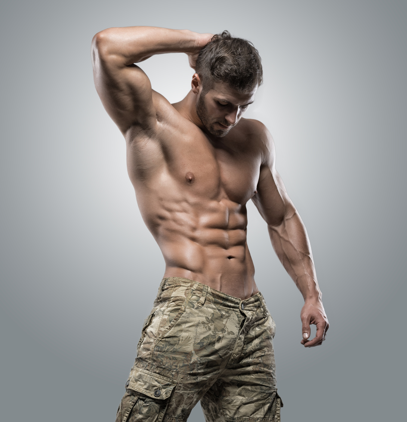 Muscular athlete bodybuilder man on a gray background