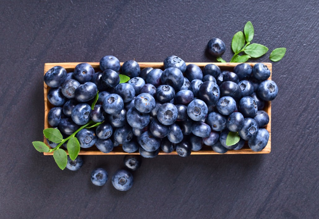Blueberries in old wooden dish .