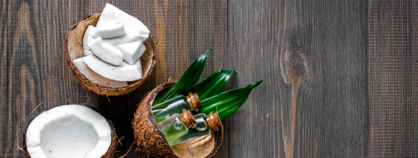Skin care. Coconut lotion on wooden table background top view copyspace