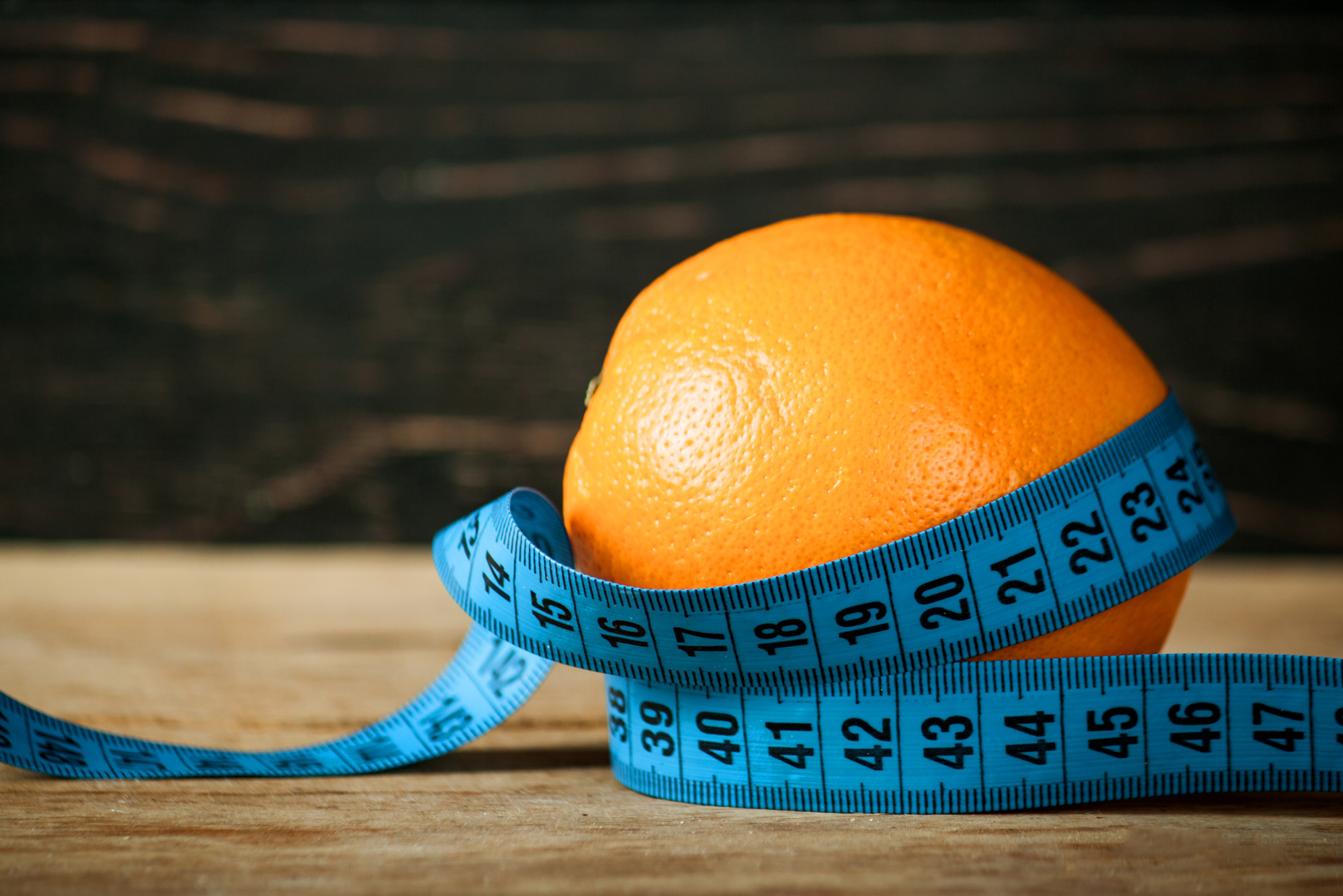 Fresh orange and measuring tape