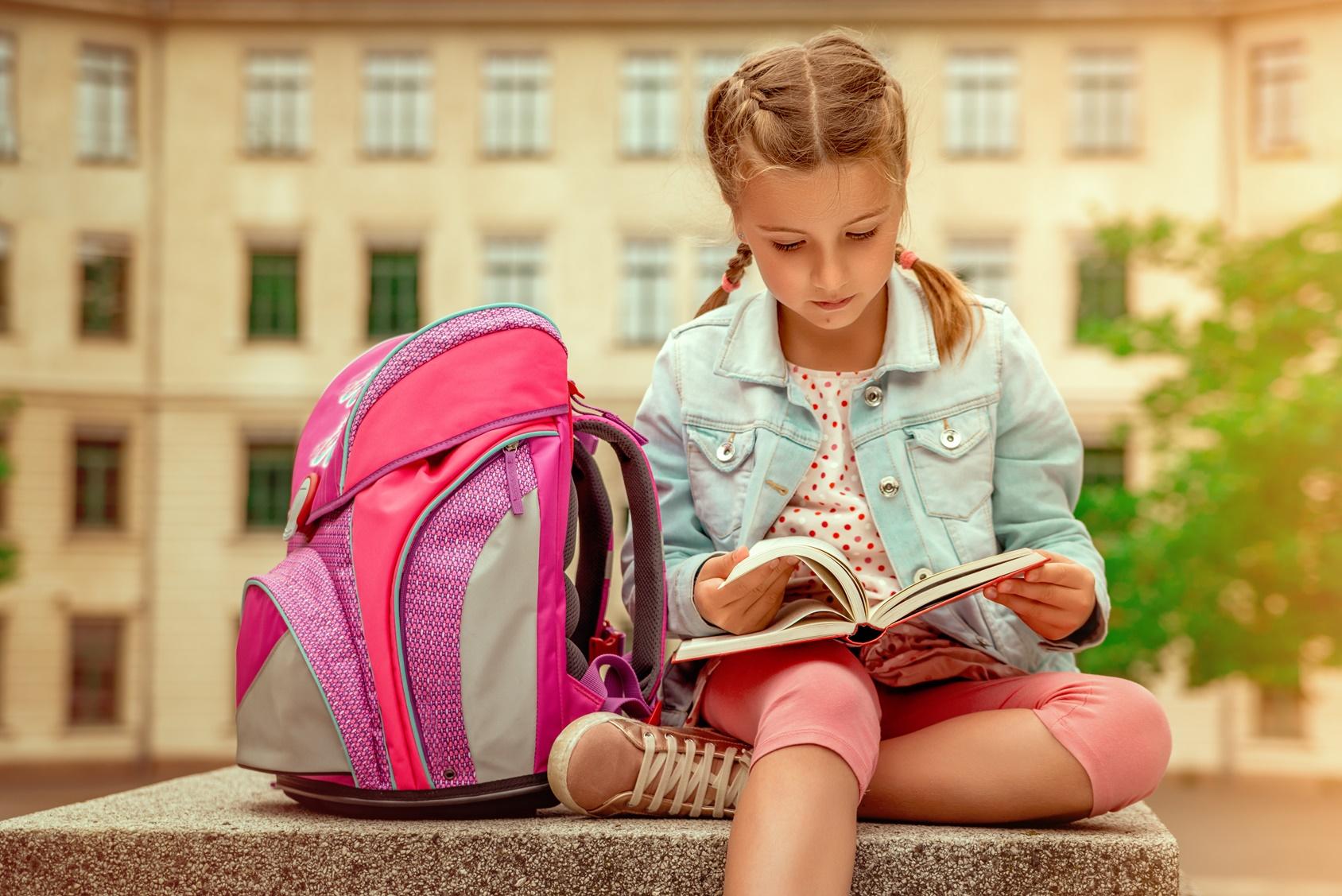 kind liest vor der schule