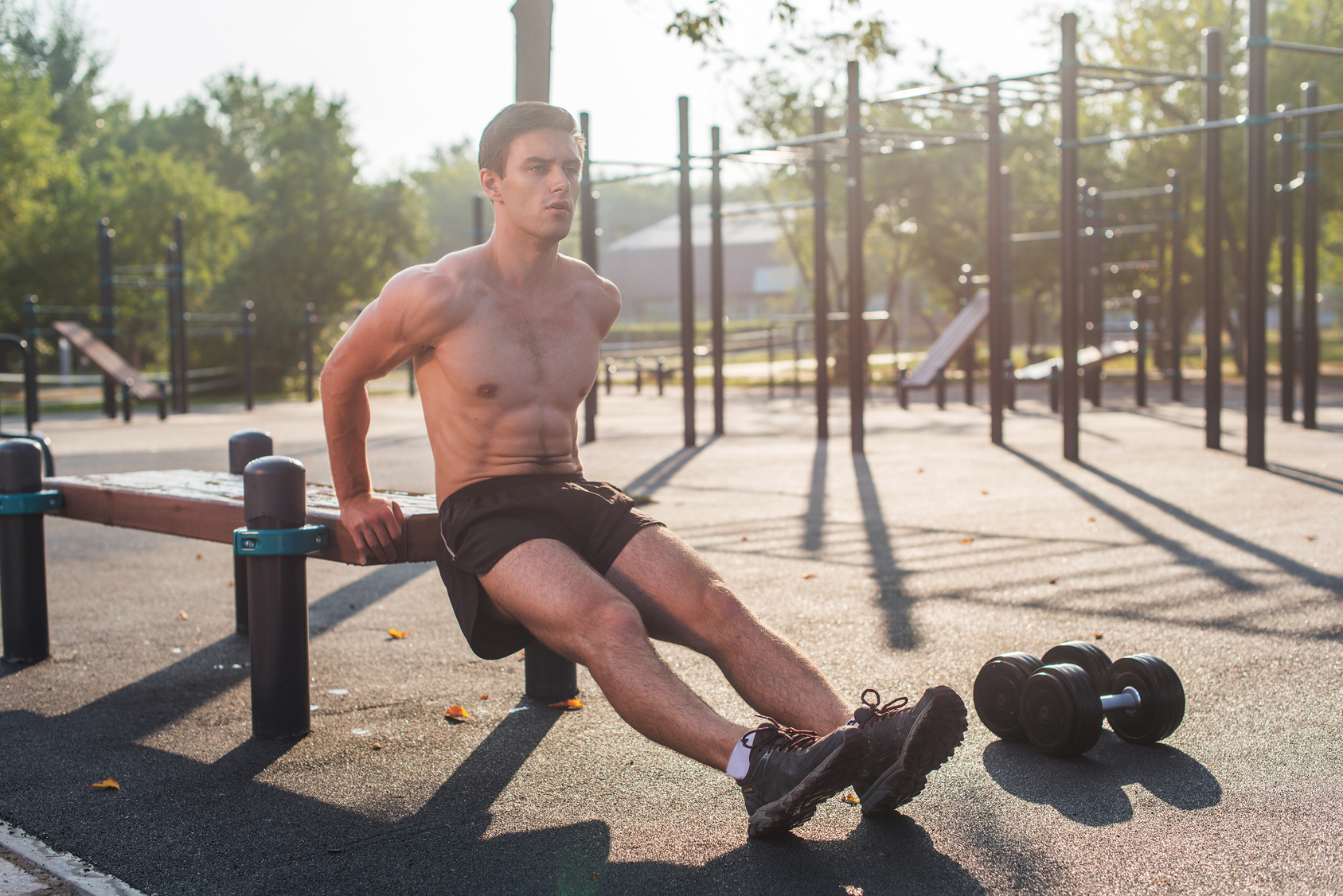 Young fit man doing triceps dips exercises during outdoor cross training workout. Fitness male model.