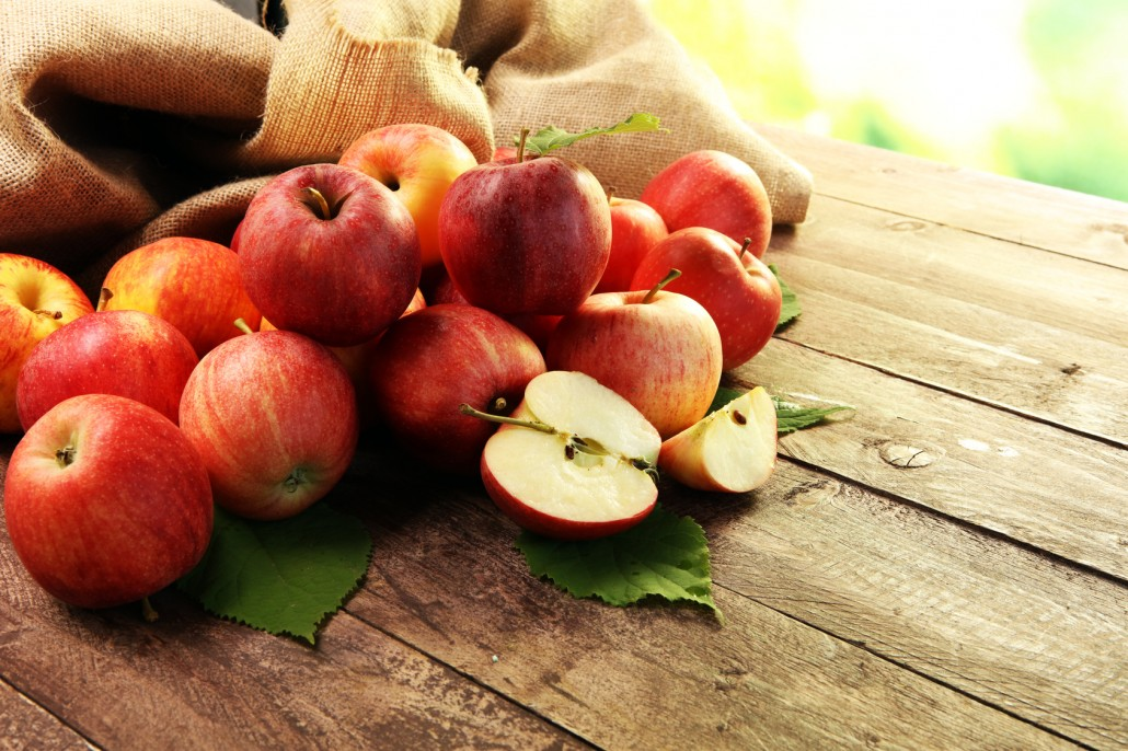 Ripe red apples with leaves on wooden background