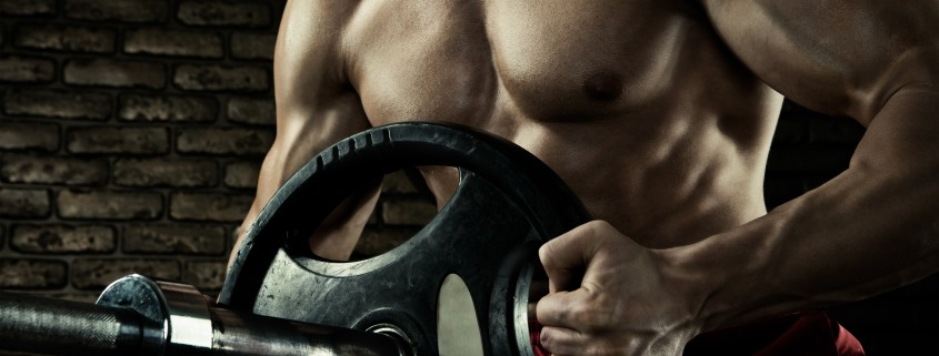 Sports background. Closeup photo of handsome bodybuilder guy prepare to do exercises with barbell in a gym, keep barbell plate in hands