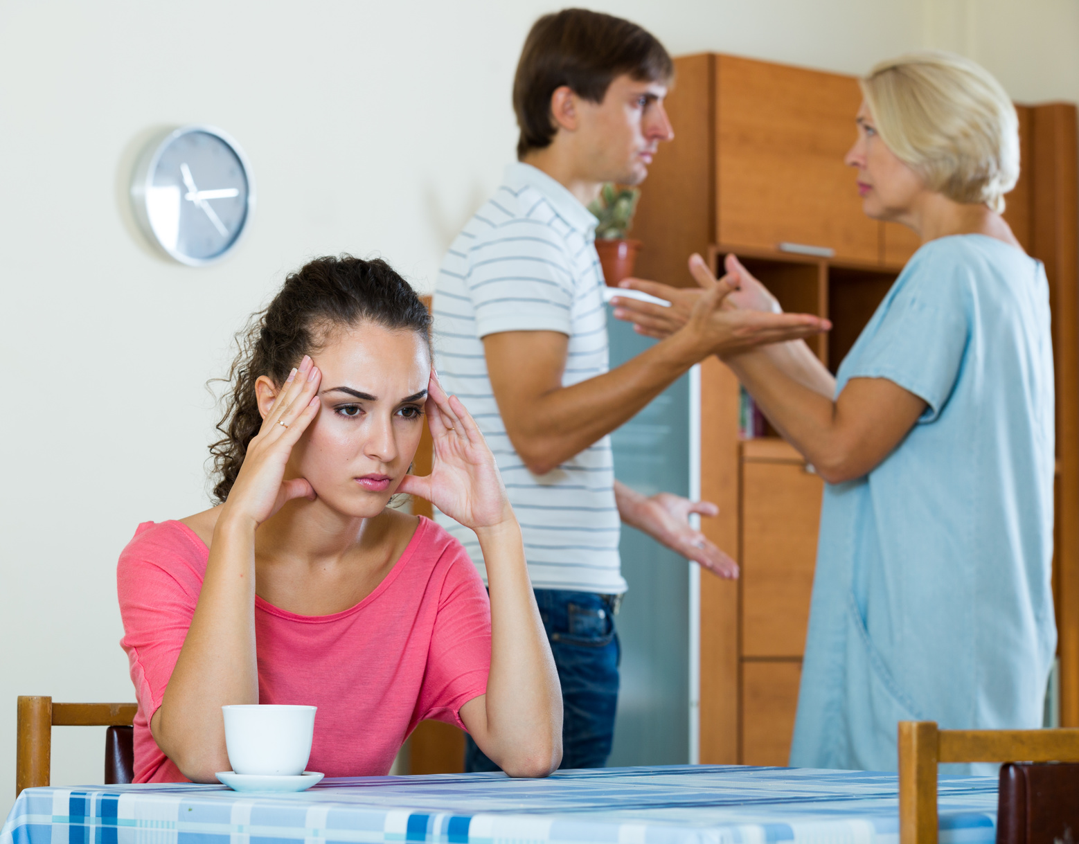 Sad young woman watching husband and mother having fight