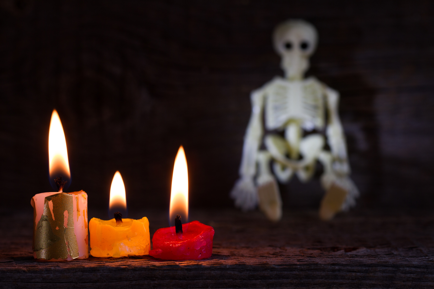 Halloween abstract background with skeleton and candles on cemetery