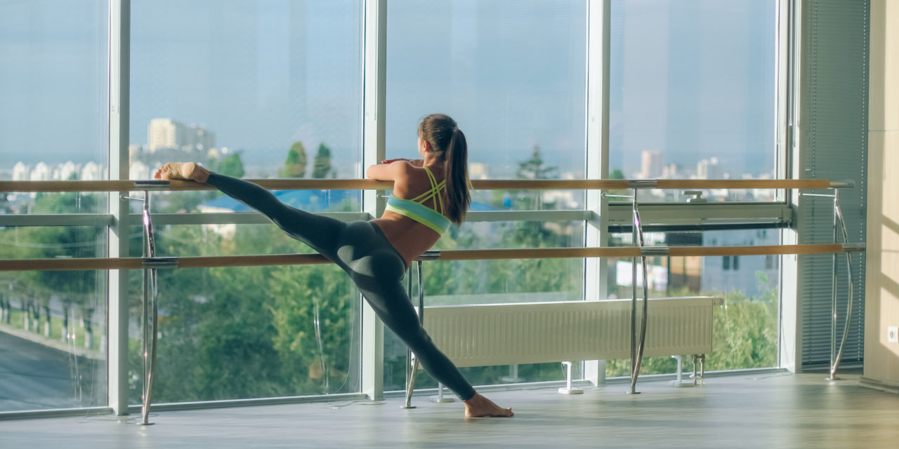Woman stretching her leg at the barre