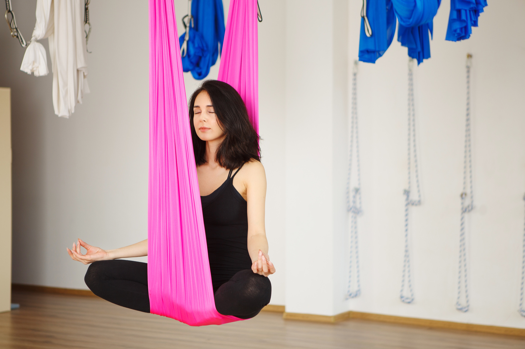 Woman sits in lotus pose in hammock practicing aerial yoga