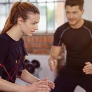 trainer betreut eine kundin beim ems-training im studio