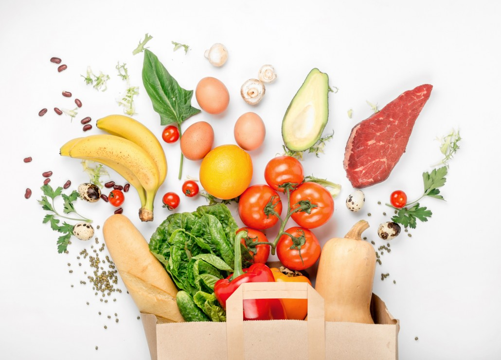 Full paper bag of different health food on white background