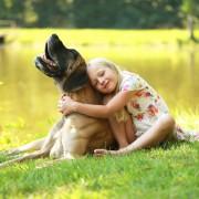glückliches Mädchen mit ihrer Dogge am See