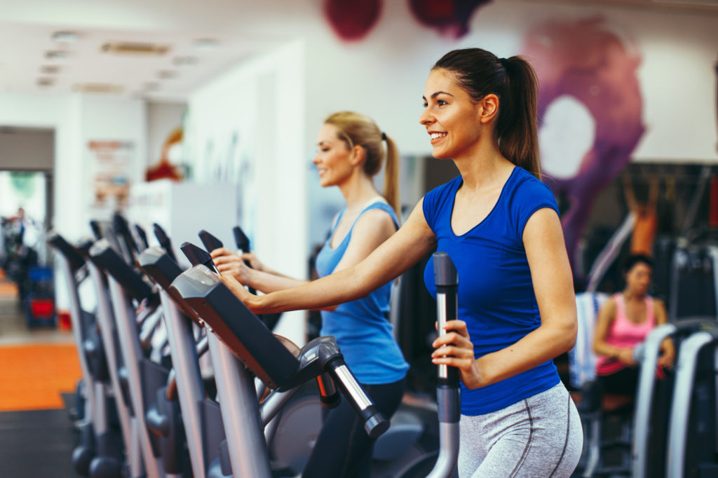 Two young woman exercising on stepper machine at gym