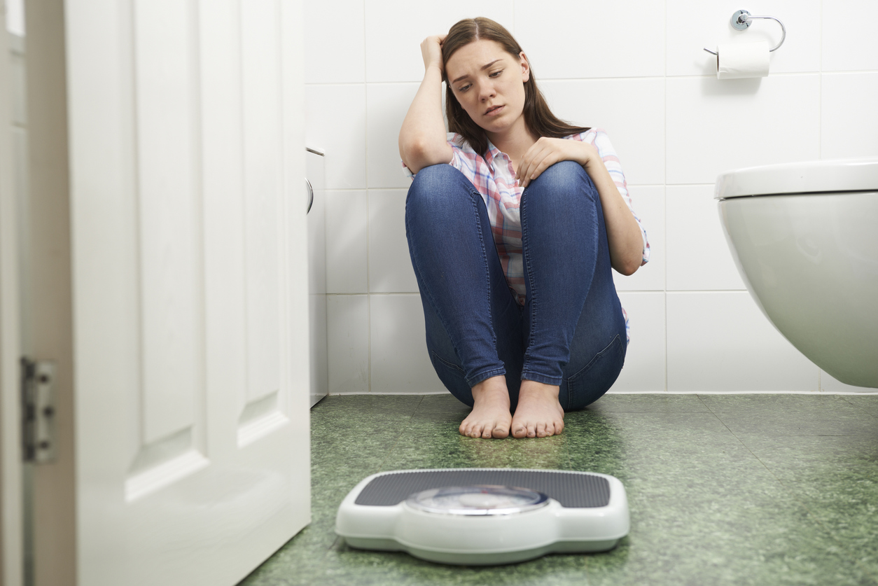 Unhappy Teenage Girl Sitting On Floor Looking At Bathroom Scales