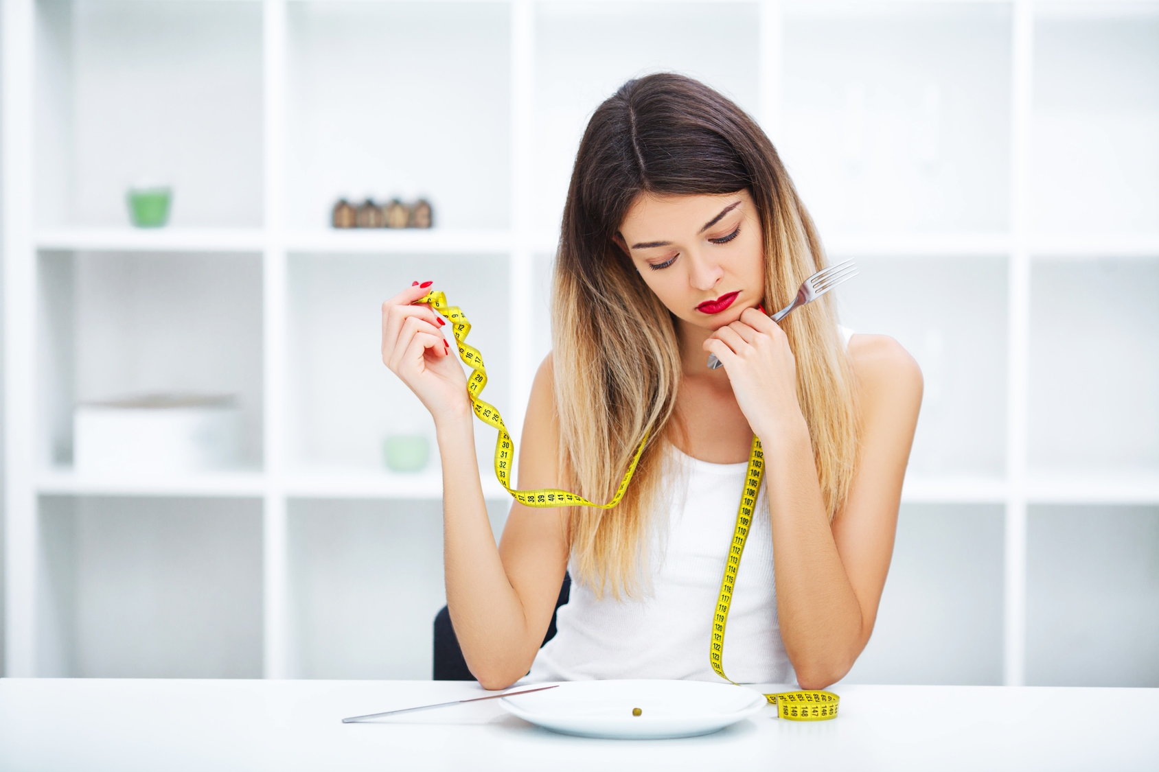 Diet. Eating disorder. Girl is holding a plate and trying to put a pea on the fork