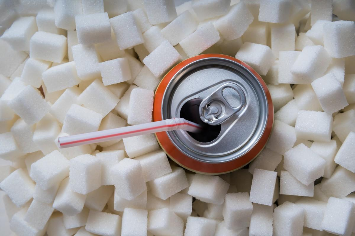 Carbonated soda drink with many sugar cubes. Unhealthy eating concept.