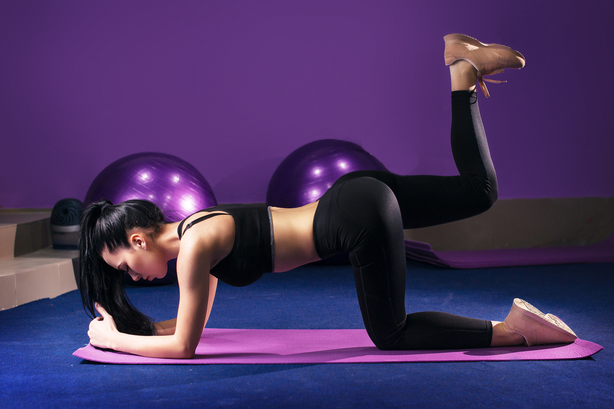 woman on Abdominals workout posture in gym . Plank Bent Leg Raise