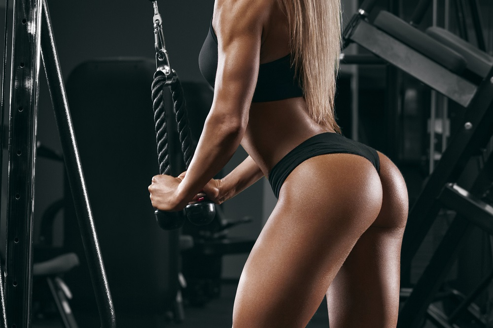 Athletic girl working out in gym. Sexy beautiful butt in thong. Fitness woman doing exercise