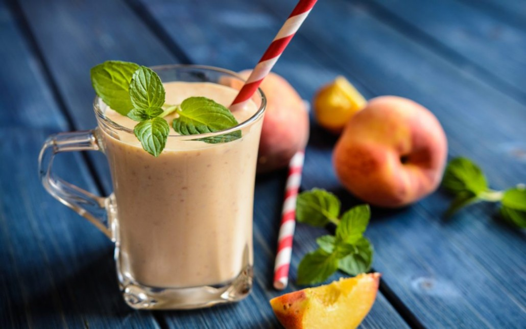 Healthy peach milkshake in a glass jar