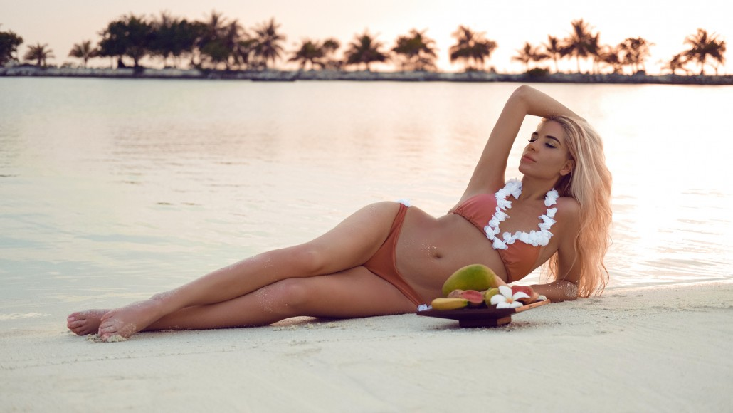 Carefree blonde woman lying on white sand Enjoying Beautiful Sunset on Tropical Beach. Sexy bikini model with exotic fruits over hawaii exotic background.