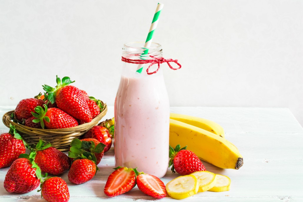 Strawberry and banana smoothie or milkshake with a straw in a bottle