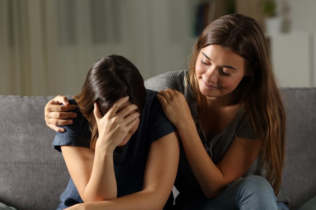 Bad hypocrite friend comforting a sad girl
