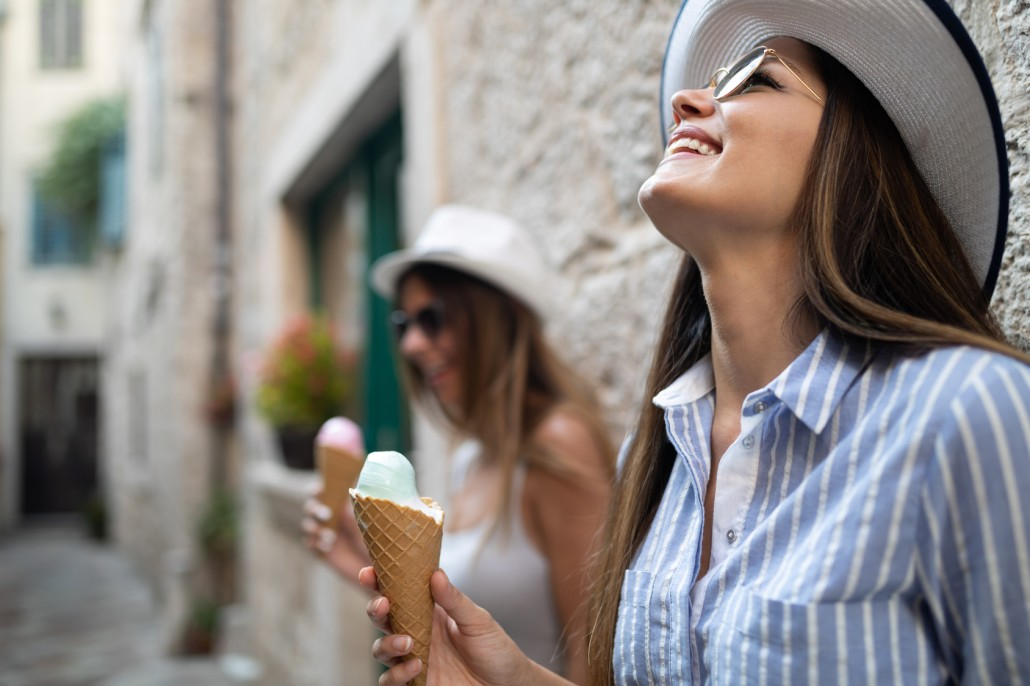 Two young female friends having fun and eating ice cream.