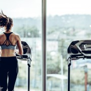 Attractive woman running on treadmill in sport gym