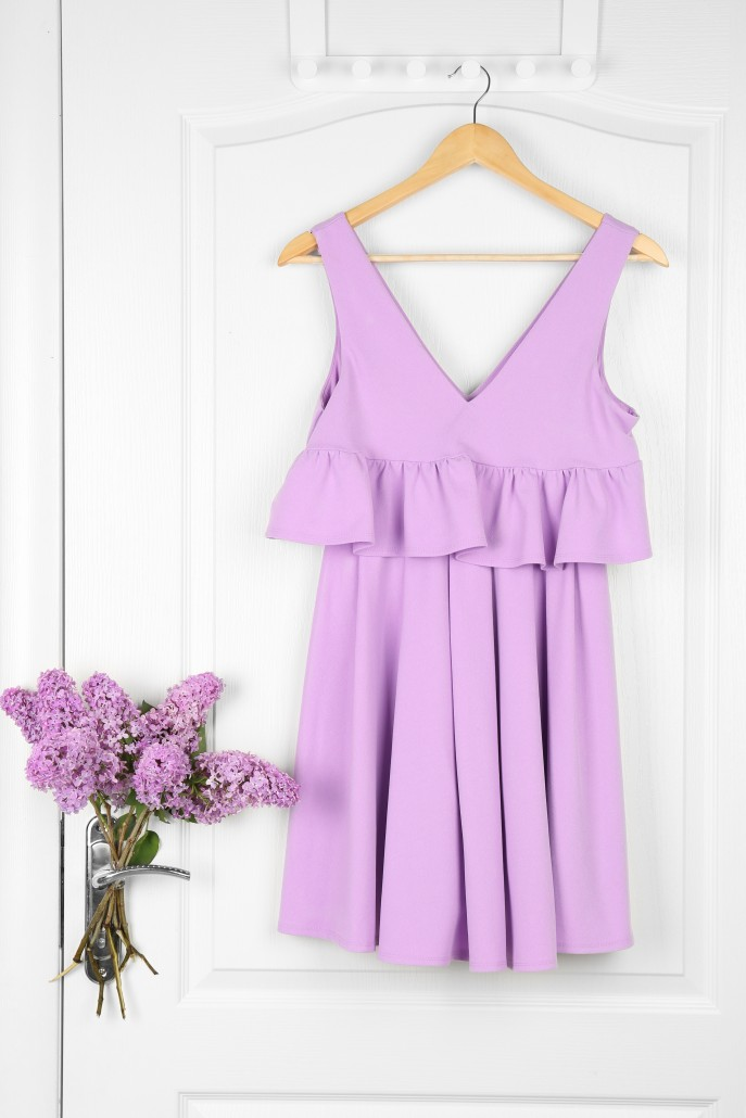 Trendy dress and branches of lilac hanging on white door